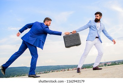 Businessman takes away briefcase from business partner. Fraud and extortion concept. Men suits handover briefcase. Rascal racketeer extortionist cheating business transaction. Risky transaction.