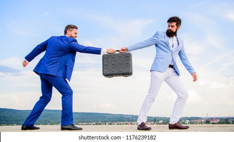 Businessman takes away briefcase from business partner. Men suits handover briefcase. Rascal racketeer extortionist cheating business transaction. Risky transaction. Fraud and extortion concept.