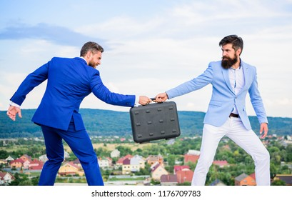 Businessman takes away briefcase from business partner. Fraud and extortion concept. Rascal racketeer extortionist cheating handover. Men suits handover briefcase. Business deal landscape background.