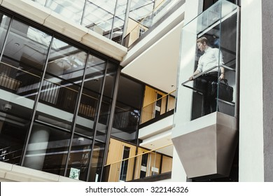 Businessman taking modern glass elevator to the upper floors