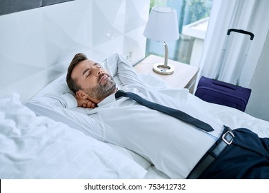 Businessman taking nap and relaxing in hotel room after travelling on work trip