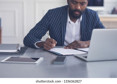 Businessman taking notes in front of the laptop in the modern office space.