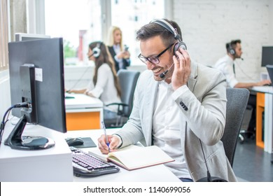 Businessman taking notes while talking with customer using headphones and microphone in call center