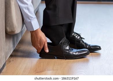 Geschäftsmann, der nach der Arbeit zu Hause Schuhe anzieht