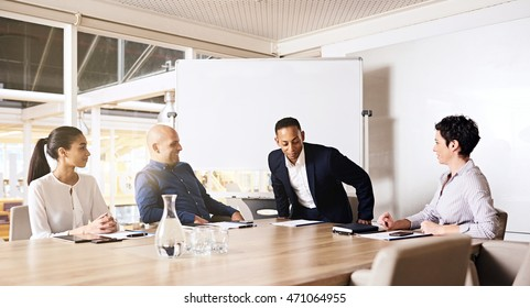 Businessman taking a seat at the head of a board room table next to one of his female colleagues, ready to collaberate with all 3 other business executives that were already seated, waiting and ready