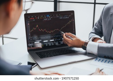 Businessman talking about investment stock market and graph from computer laptop with broker trader, giving money plan management and analysis