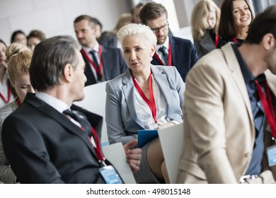 Businessman talking to businesswoman in seminar hall at convention center