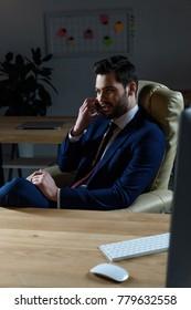 businessman talking by smartphone in dark office