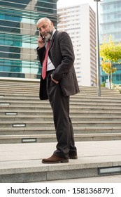 Businessman talking by smartphone and smiling at camera. Full length view of mature bearded businessman standing with hand in picket and talking by cell phone on street. Connection concept