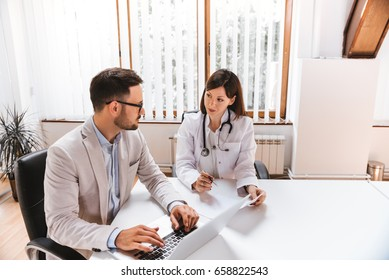Businessman talking with female doctor at the hospital