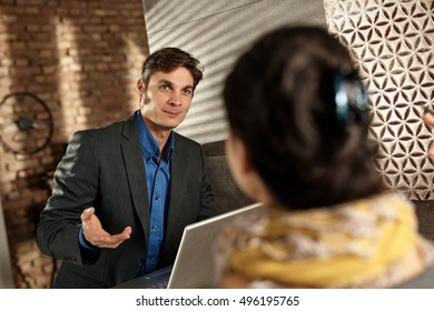 Businessman talking to female partner, using laptop.