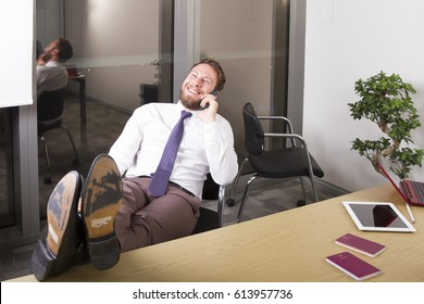 Businessman talking with mobile, drinking coffee, searching on tablet while seating and relaxing.