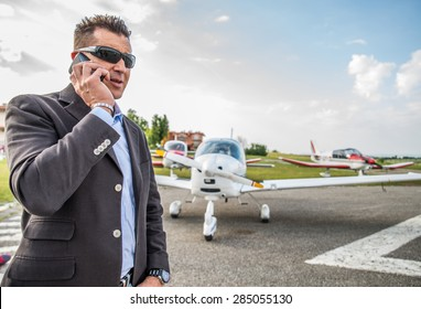 Businessman talking at mobile phone at the airport - Business man taking a private charter airplane for affairs.Handsome man wearing suit jacket outdoors