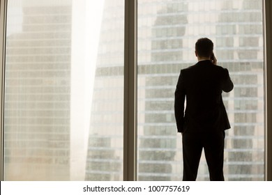Businessman talking on cellphone while standing neal large window in office and looking on urban landscape. Financial director having phone conversation with business partner, calling home. Back view