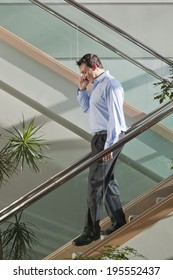 Businessman talking on mobile phone while walking down stairs