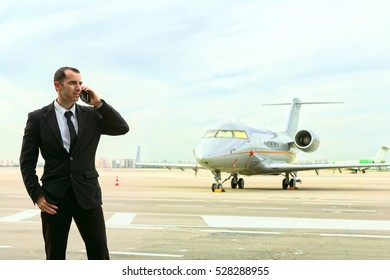 Businessman talking on mobile phone in front of aircraft