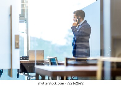 Businessman talking on a mobile phone while looking through modern corporate office window.
