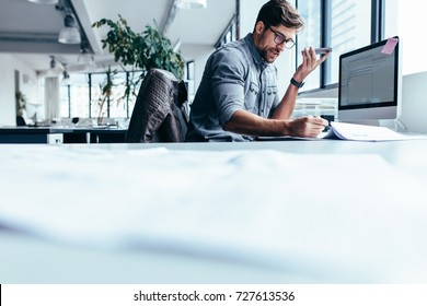 Businessman talking on mobile phone and looking at documents. Young male executive working in office.