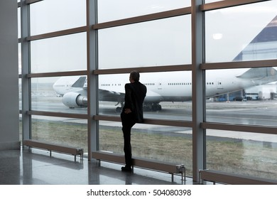 Businessman talking on the  phone at airport terminal