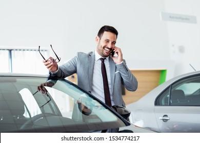 Businessman talking on phone near car in modern dealership.