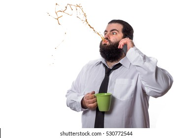 Businessman talking on the phone receives a news that surprises him and spits out the coffee he is drinking isolated on white background