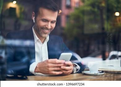 Businessman talking  on phone through wireless headphones in cafe