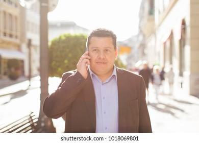 Businessman talking on the phone. Urban background.