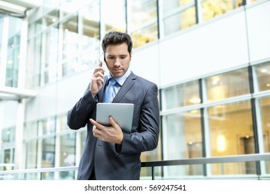 Businessman talking on phone and using a tablet pc
