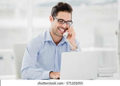 Businessman talking on phone and using laptop in office