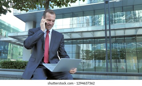 Businessman Talking on Phone while Working on Laptop Outside Office