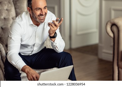 Businessman talking on phone and working on laptop while sitting in hotel room. Smiling businessman working from hotel room on business trip.