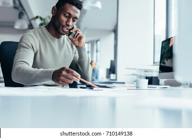 Businessman talking on smartphone and working in office. African male architect sitting at his workplace.