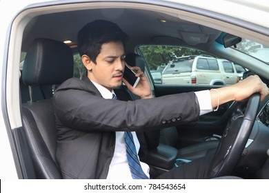 Businessman talking on the telephone in the car comfortably.