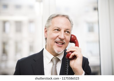 Businessman talking on a vintage phone in his office