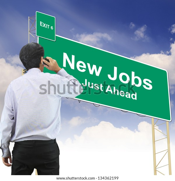 Businessman talking the phone standing in front Road sign concept with the text New Jobs