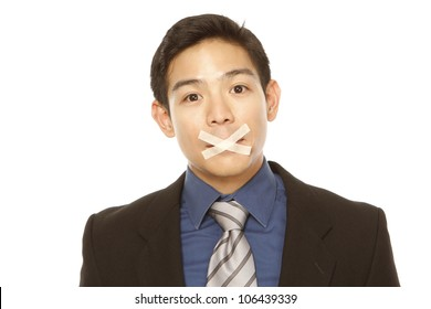 A businessman with tape over his mouth (isolated on white)