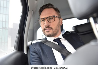 Businessman in taxi cab looking by car window