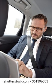 Businessman in taxi cab reading news on digital tablet