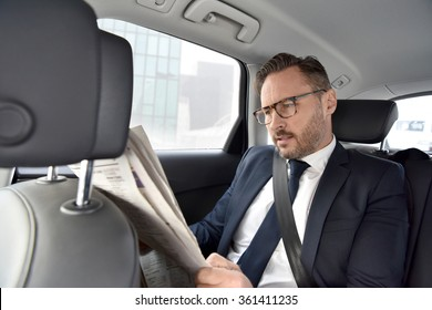 Businessman in taxi cab reading newspaper