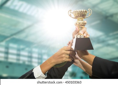 Businessman team holding award trophy for show their victory.