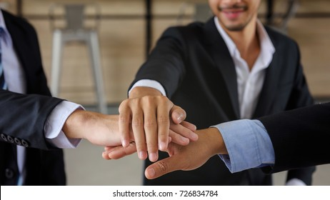 businessman team joining and shaking hands together with smile face after getting agreement on project. symbol of teamwork ,companionship, unity for Business success.