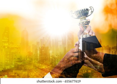 Businessman team show trophy for joyful together after successful business.Team work concept.