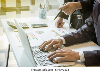 Businessman team working at office desk and using a digital touch screen tablet hands detail, computer and objects on the table in morning light.