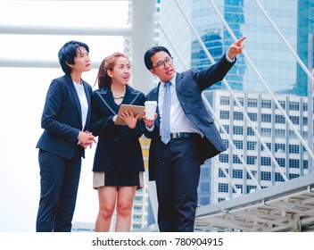 Businessman and teamwork. She play smart phone and talking on town background. He is pointing in to sky and talking Business . Photo concept team work and Business.