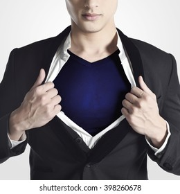 businessman tearing his shirt and showing a superhero suit underneath his suit, isolated on white background