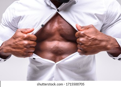 Businessman tearing off his shirt and showing mucular body on background