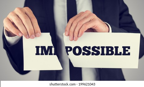Businessman tearing up a sign saying - Impossible - conceptual of successfully overcoming problems and challenges and positive attitude , retro effect faded look.
