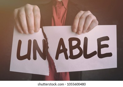 Businessman tearing up a sign saying Unable and changing word unable into able. Conceptual image of positive motivation, finding solutions and transformation.