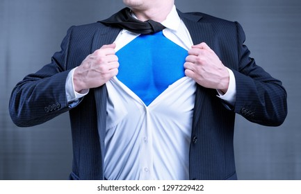 Businessman tears shirt on himself to show that he is Superman isolated on background