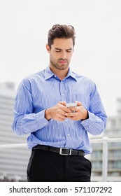 Businessman text messaging on mobile phone on office terrace